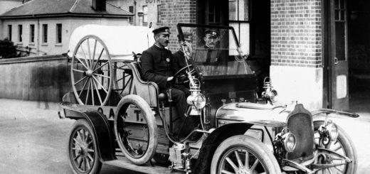 Drei Männer in Uniform sitzen auf dem Vordersitz eines offenen, historischen Automobils.