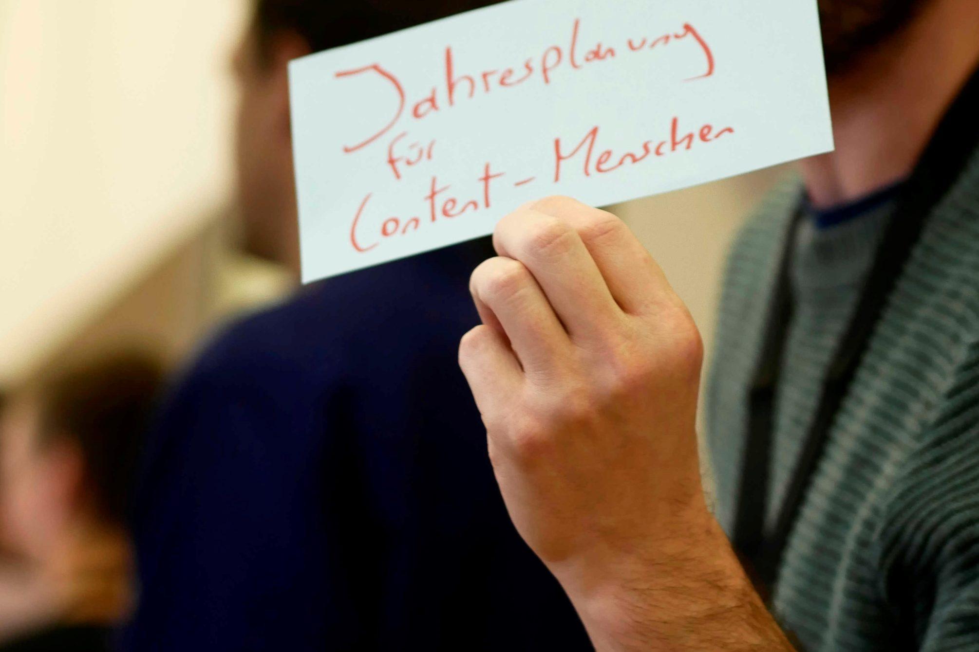 """Zettel in der Hand gehalten mit der Aufrschrift """"Jahrsplanung für Content-Menschen"""""""